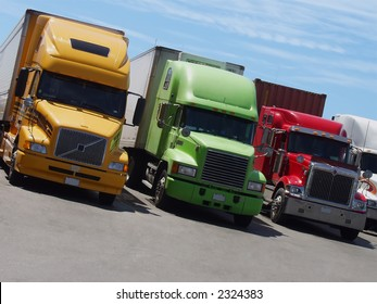 Yellow, green and red semi-trailer trucks stand side-by-side at a rest area in North America.