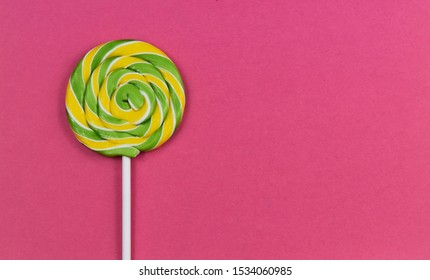Yellow green spiral lollipop stock images. Colorful round lollipop on a pink background. Candy on a pink background with copy space for text