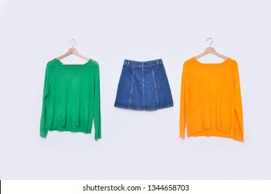 yellow and green sweater denim on hanging and skirt jeans on white background