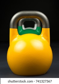 Yellow, green and white competition kettlebells lined up in a row on a weight training gym floor. Yellow competition kettlebells weigh 16kg. Green kettlebells weigh 24kg. White kettlebells weigh 10kg.