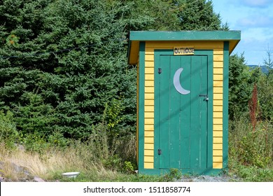 A yellow and green wooden building with as sign that spells out outhouse over the green door in among trees. The outdoor toilet has a moon shape on the exterior side of the door.