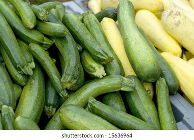 Yellow and green zucchini piled high at a market.