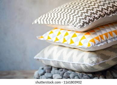 Yellow and grey pillows on the wall background. Close up