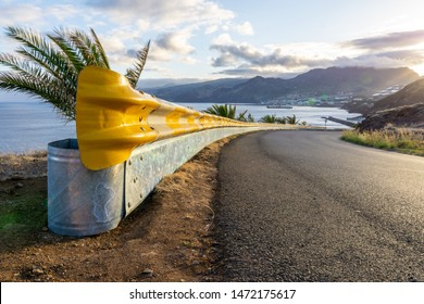 Yellow guardrail along curvy road with sunset over the sea and village
