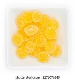 Yellow gum drops in a white bowl in top view