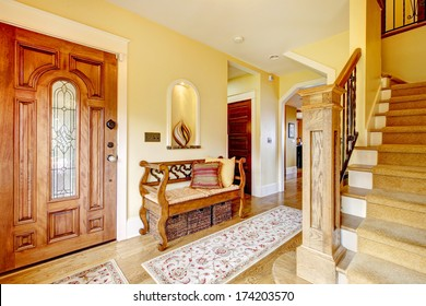 Yellow hallway with hardwood floor, stairs and rustic wood hallway storage seat