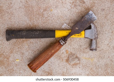 Yellow Hammer and and chisel tool placed on concrete floor.