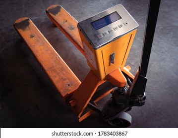 Yellow hand pallet truck or manual hand lift with digital weigh scales.