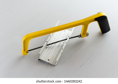 yellow hand saw and aluminium miter box for hobby in home workshop.
