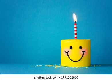 Yellow happy face birthday cake with one candle