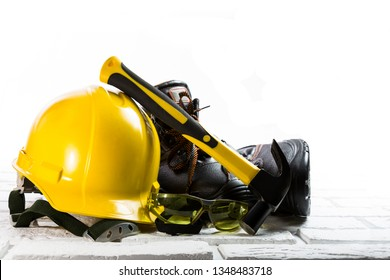 Yellow hard hat, black work boots, goggles and a hammer on white bricks