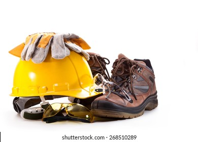 Yellow hard hat of the builder, goggles, gloves and boots on a white background