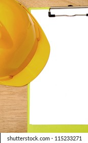 Yellow hard hat and clipboard. You can put your design on the clipboard