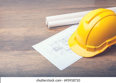 The yellow Hard hat construction plans on wooden board. Shows the concept of architects and builders who are designing and building houses.