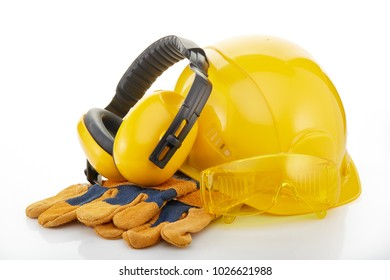 Yellow hard hat, earphones, goggles and gloves on a white background