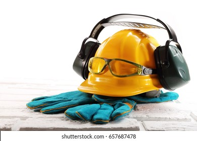 Yellow hard hat with headphones against noise, goggles and gloves on white bricks