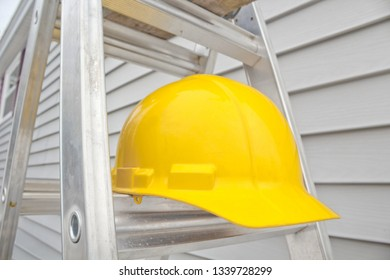 Yellow hard hat on stepladder with house siding in background.
