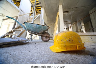 Yellow hard hats and small cart on concrete floor inside unfinished building