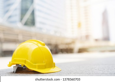 yellow hard safety wear helmet hat in the project at construction site building on concrete floor on city with sunlight. helmet for workman as engineer or worker. concept safety first.