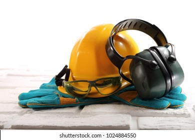 Yellow hardhat with goggles, headphones and gloves on white bricks