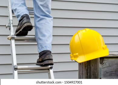 Yellow hardhat on railing post with worker's legs on ladder in background.