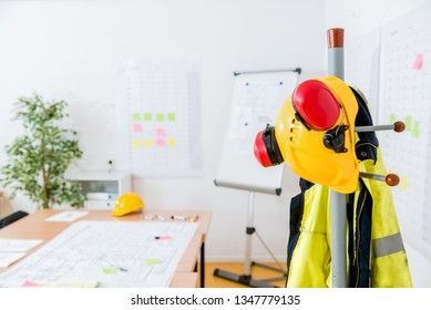 Yellow hardhat and red earmuffs on rack in contractor's office