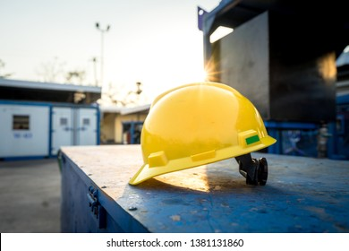 Yellow hardhat or safety helmet (no logo) for technician worker is placed on toolbox at workshop yard with sun light flare. Safety, no accident in workplace concept photo.
