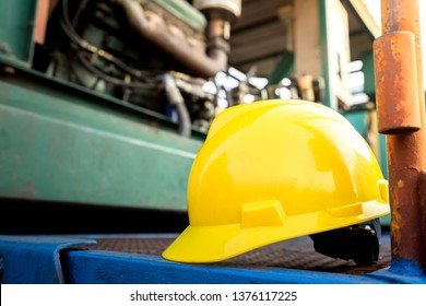 Yellow hardhat or safety helmet is placed on working platform of pumping unit in oil field operation. Selected focus on the hard hat. Safety, no accident in workplace concept photo.