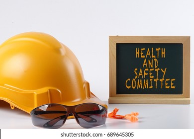 Yellow hardhat safety helmet,safety glass and ear plug isolated on white background with HEALTH AND SAFETY  COMMITTEE words. Industrial safety and health conceptual.