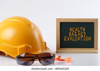 Yellow hardhat safety helmet,safety glass and ear plug isolated on white background with HEALTH HAZARD EVALUTION words. Industrial safety and health conceptual.
