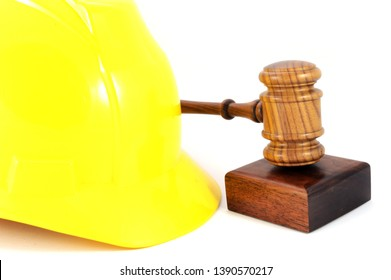 A yellow hardhat and wooden gavel for labour law concepts and legalities in the workplace of a construction zone.