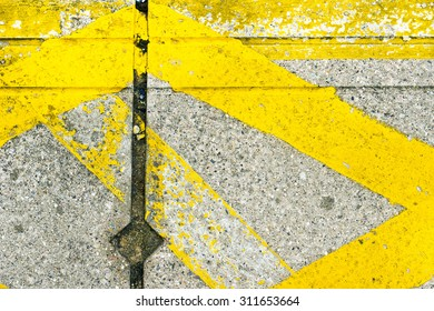 Yellow hazard lines painted on a stone surface