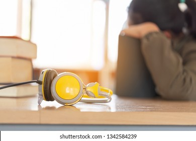 Yellow headphone on book in cafe or library, morning light.