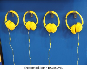 Yellow headphones on a light blue background.