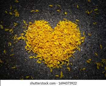 Yellow heart made of flower petals on dark background closedup, heart shape, the concept of mourning, grief or sorrow.