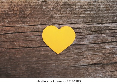 Yellow heart on wooden background