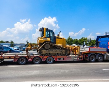 Yellow heavy duty crawler bulldozer on truck trailer in traffic - Transporting bulldozer excavator in everyday street traffic - Tractor bulldozer with caterpillar drive no truck