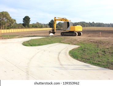 Yellow heavy duty earth moving machine on site in a new real estate subdivision in australia excavating the land ready for housing development.....DP