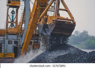 Yellow heavy excavator and bulldozer unloading road metal during road construction work