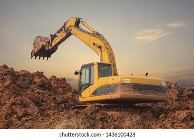 Yellow heavy excavator excavating earth and stone