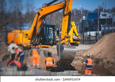 Yellow heavy excavator excavating sand and working during road works, unloading sand during construction of the new road with workers around