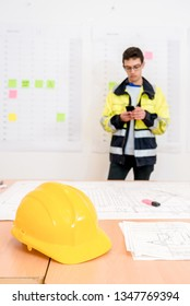 Yellow helmet and blueprints on table with contractor using smartphone in office
