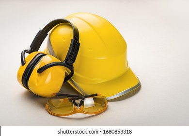 Yellow helmet and earphones with goggles on a light background: personal health and safety equipment concept.