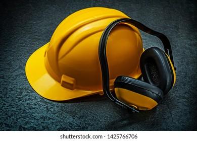 yellow helmet and earphones on blackbackground