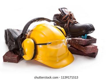 Yellow helmet with glasses for eye protection, headphones, black boots, bricks