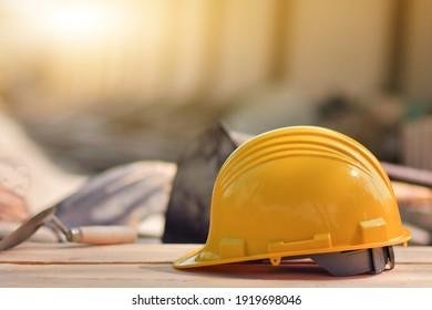 Yellow helmet hard hat  on wood floor in constriction site