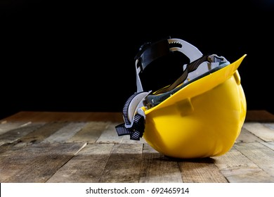 Yellow helmet on an old wooden table. Workshop in the workshop. Wooden table, black background.