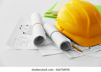 Yellow helmet on the table with blueprints
