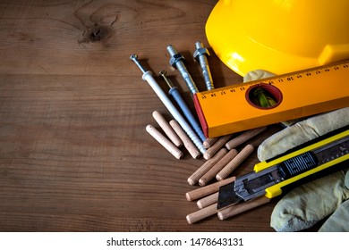 yellow helmet, protective gloves, level, model knife and dowels  on wooden background