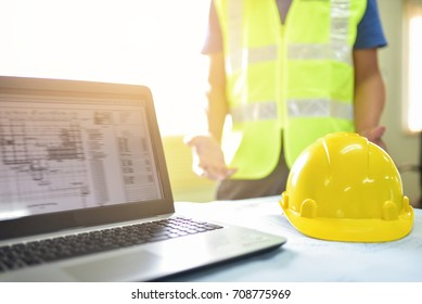 Yellow helmet put on the table and manager engineer or safety officer blurred acting background on construction site engineering construction concept